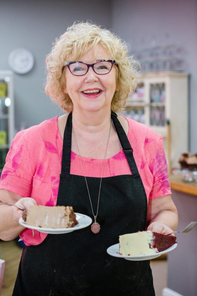 lady-smiling-whilst-holding-plates-of-cakes