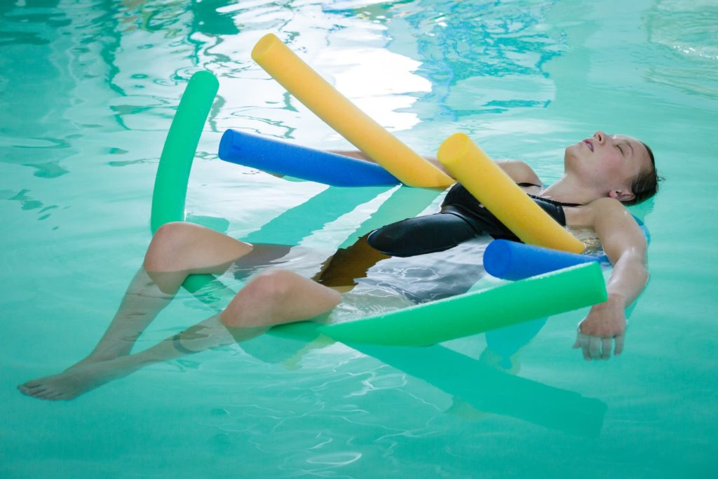 pregnant-lady-laying-on-back-in-pool-with-floats