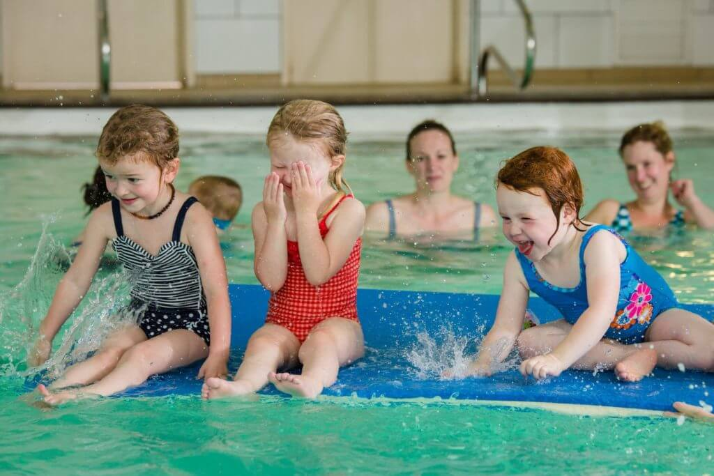 toddlers-splashing-on-a-float-in-a-swimming-pool