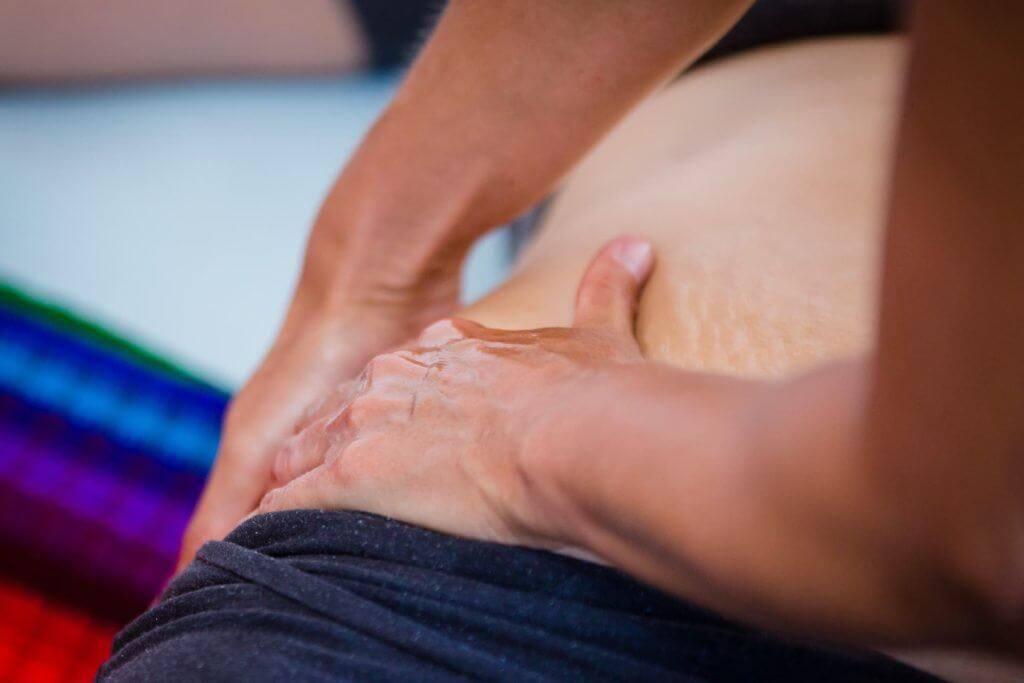 womans-hands-massaging-a-ladys-hips